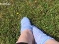 Kleine stinkende Füße in Socken draußen